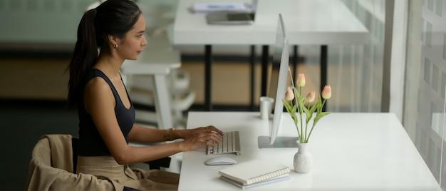 Портрет женщины-предпринимателя, улыбаясь и скрестив руки, сидя за рабочим столом в офисе со стеклянной перегородкой