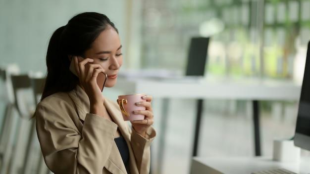사무실 방에서 커피 휴식을 취하는 동안 전화로 이야기하는 여성 기업가의 초상화