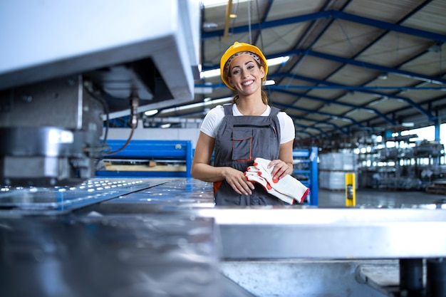 生産ラインで産業機械のそばに立っている保護制服とヘルメットの女性工場労働者の肖像画