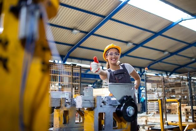 엄지 손가락을 들고 산업 기계에 의해 서 여성 공장 노동자의 초상화.