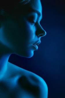 黒のネオンライトで女性のファッションモデルの肖像画