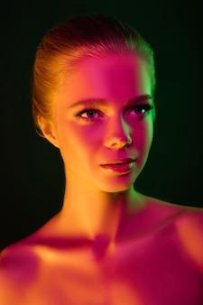 Портрет женской фотомодели в неоновом свете на темной предпосылке студии.