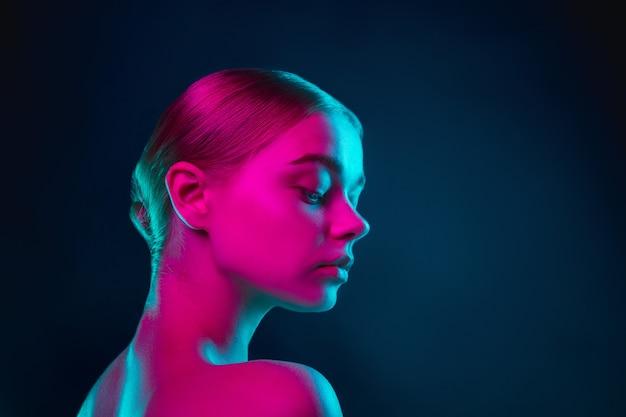 暗いスタジオのネオンライトで女性のファッションモデルの肖像画
