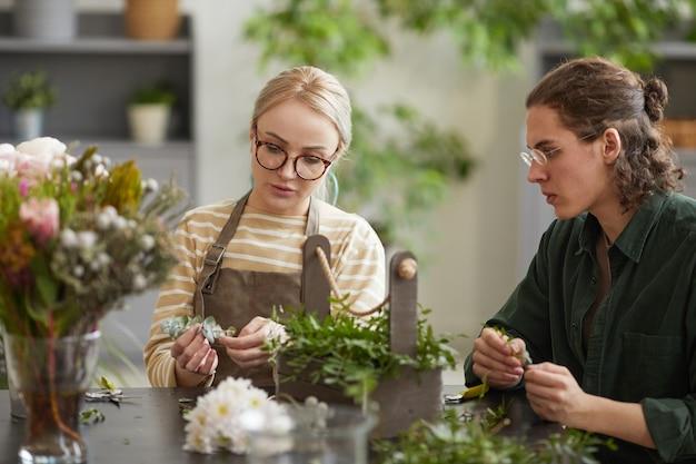 ワークショップ、コピースペースで花の組成物を作成しながら若い男を教える女性の花屋の肖像画