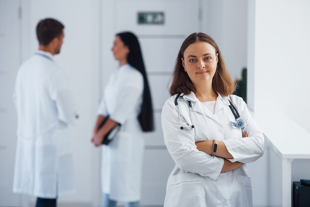 여성 foctor의 초상화는 뒤에 직원과 함께 병원에 서 있습니다.
