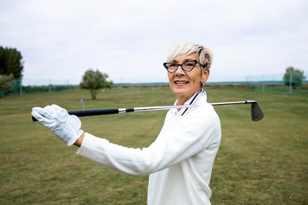 골프 코스에 골프 클럽이 서 있는 여성 골퍼의 초상화.