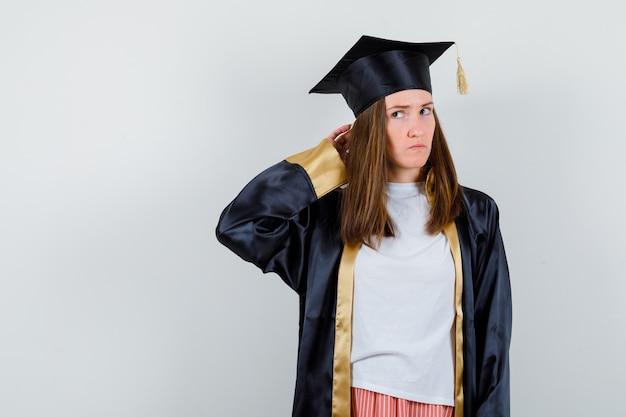 制服、カジュアルな服装で頭の後ろで手をつないで、物思いにふける正面図を探している女性の卒業生の肖像画
