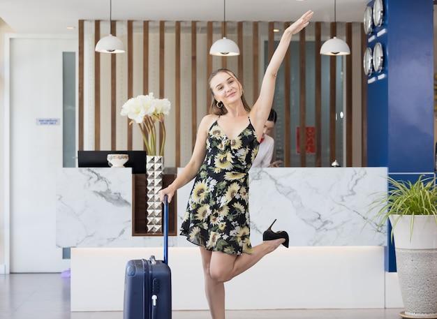 ホテルでチェックインを待っている荷物を持つ女性のゲストの肖像画、幸せな旅行ライフスタイルのコンセプト