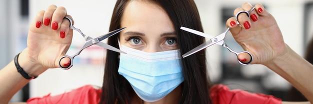 Портрет женщины-парикмахера в защитной медицинской маске, держащей ножницы