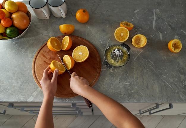 Портрет женских рук, разрезающих апельсины пополам на деревянной кухонной доске. приготовление свежевыжатого апельсинового сока