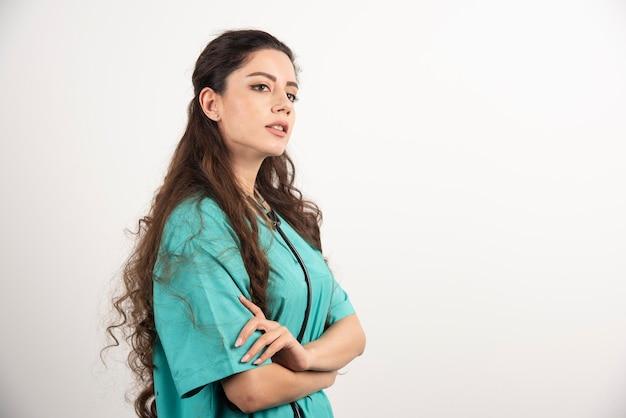 Портрет женского работника здравоохранения, позирующего со скрещенными руками.