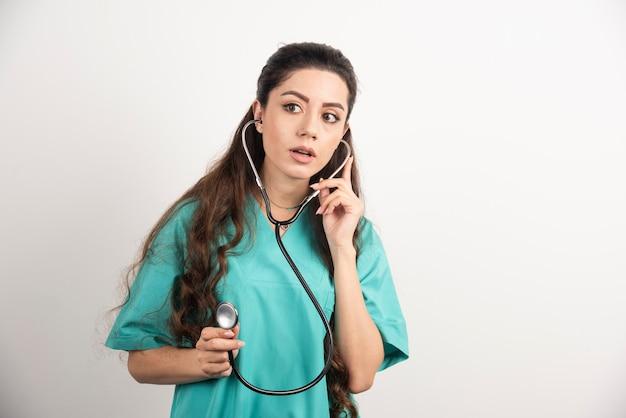 Портрет женского работника здравоохранения представляя со стетоскопом.
