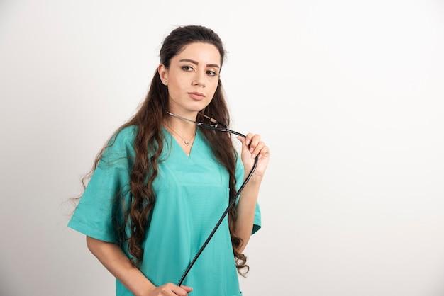 聴診器でポーズをとる女性医療従事者の肖像画。