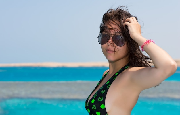 晴れた夏の日にヨットの鼻の上に立って髪を調整する黒緑色の水着の女性の肖像画、背景に美しいターコイズブルーの海