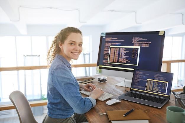 Портрет ит-разработчика женского пола, улыбающегося в камеру во время набора текста на клавиатуре с черно-оранжевым программным кодом на экране компьютера и ноутбука в современном интерьере офиса, копией пространства