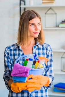 Portrait of female janitor holding cleaning equipment in the bucket