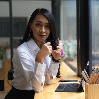 Портрет женщины, смотрящей в камеру, попивая кофе на портативном рабочем месте в кафе
