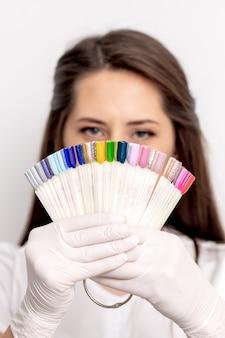 Портрет мастера женского маникюра, закрывающего лицо палитрой образцов ногтей на белом фоне