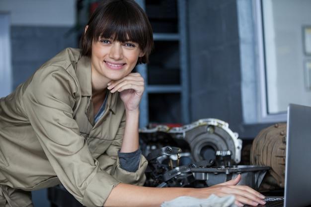 Портрет женщины механика, опираясь на стол и с помощью ноутбука
