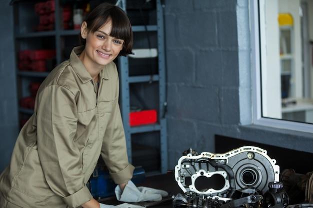 Портрет женщины механика работает над детали для автомобиля