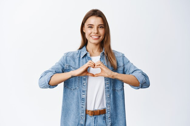 Портрет девушки-модели со светлыми волосами и белой улыбкой, любящей что-то, показывая жест сердца и улыбаясь, чтобы выразить сочувствие, стена студии