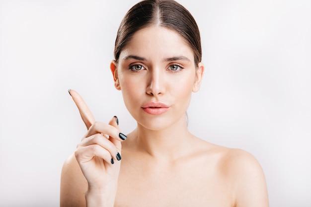 Портрет женской модели без макияжа, указывая указательным пальцем вверх на изолированной стене.