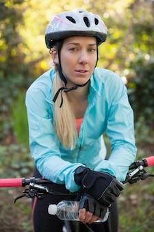 Портрет женского горного велосипедиста с велосипедом