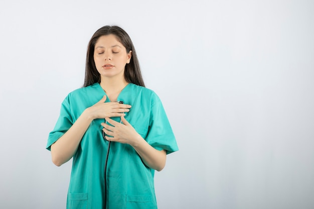 Портрет медсестры, проверяющей ее сердце с помощью стетоскопа на белом.