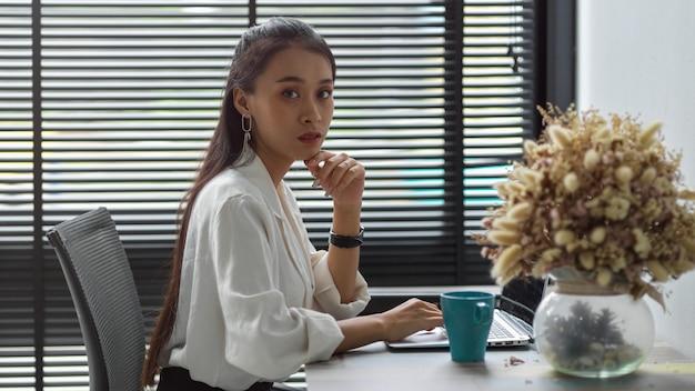 Портрет офисного работника женского пола, смотрящего во время работы с ноутбуком на офисном столе