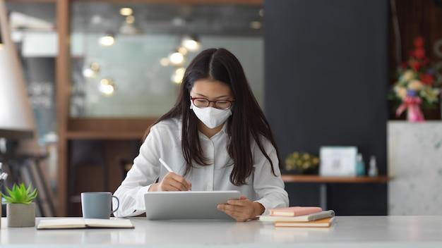 Портрет женского офисного работника в маске во время работы в офисе