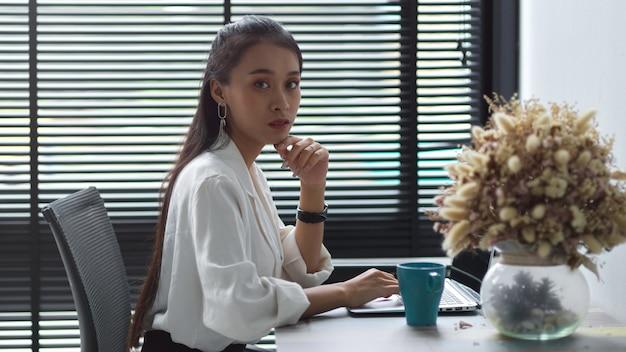 オフィスの机の上でラップトップで働く女性サラリーマンの肖像画