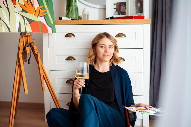 床でリラックスして白ワインを飲むウェーブのかかった髪の女性画家の肖像画。家でイーゼルの近くに座って、カメラを見ている幸せな女性。