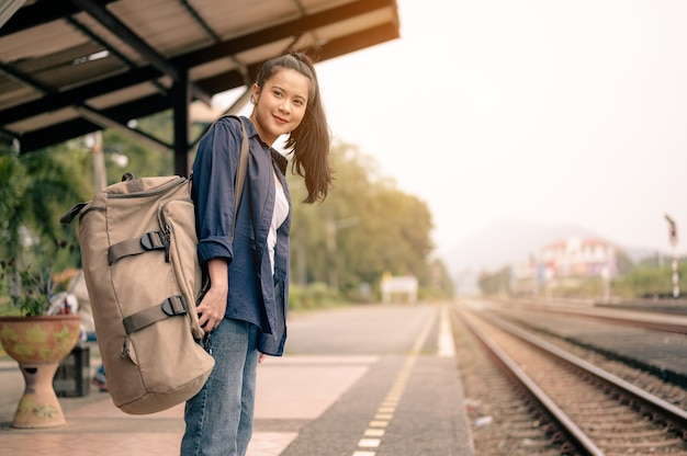 기차 타기를 기다리는 철도 플랫폼에 배낭을 메고 있는 여성 승객의 초상화. 관광, 여행 및 레크리에이션의 개념입니다.