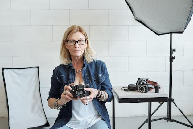빛으로 가득 찬 사진 스튜디오의 의자에 앉아 데님 옷을 입은 여성 사진 작가의 초상화