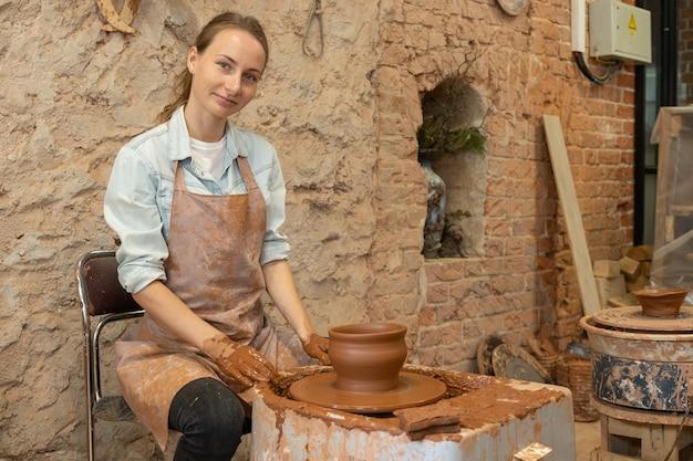 Портрет гончарного мастера в своей художественной студии. женщина-гончар в фартуке смотрит в камеру.