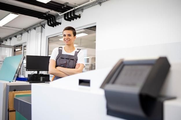 인쇄소에서 기계를 도금하기 위해 컴퓨터 옆에 서 있는 여성 인쇄 노동자의 초상화.