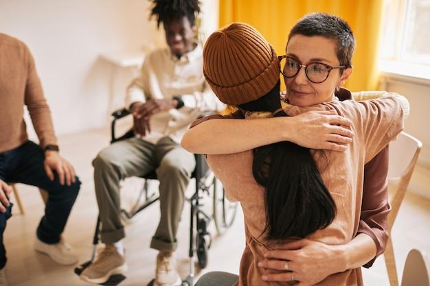 지원 그룹에서 치료 세션 동안 젊은 여성을 껴안은 여성 심리학자의 초상화, 복사 공간