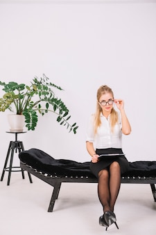 Portrait of female psychologist sitting on couch holding clipboard in hand looking through eyeglasses