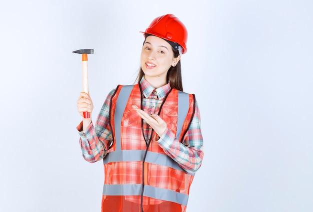Портрет женского ремонтника в униформе, стоящей с молотком над белой стеной.