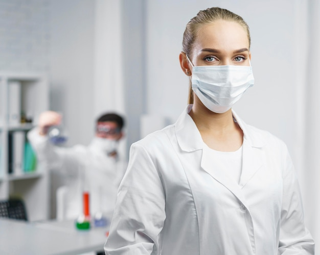 의료 마스크와 실험실에서 여성 과학자의 초상화