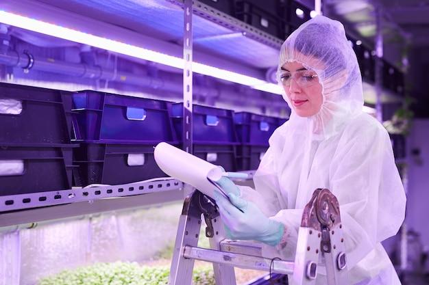 보육 온실 또는 농장 실험실에서 작업하는 동안 클립 보드에 쓰는 여성 과학자의 초상화, 복사 공간
