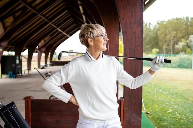 스윙을 한 후 공을 보고 있는 여성 수석 골프 선수의 초상화.
