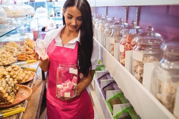 カウンターでトルコのお菓子の瓶を保持している女性の店主の肖像画