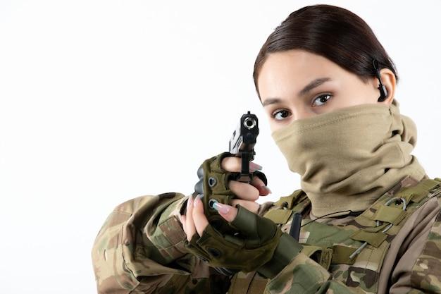 위장 흰 벽에 총을 가진 여성 군인의 초상화
