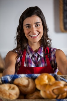Портрет женского персонала, держащего корзину сладких продуктов