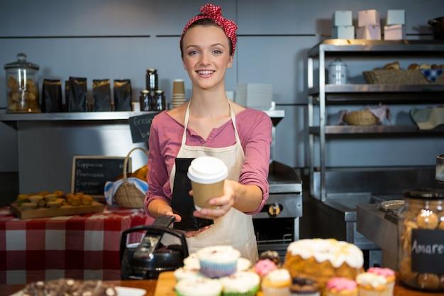 Портрет женского персонала, держащего кофейный пакет и кофейную чашку за стойкой