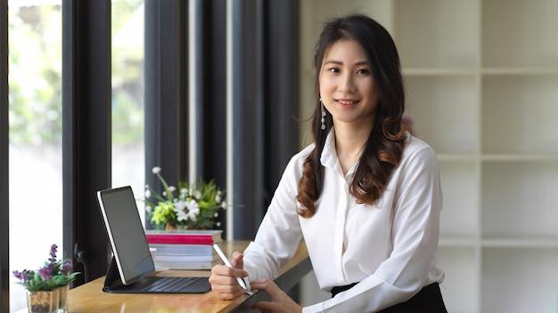 Портрет студентки, выполняющей задание с цифровым планшетом в кафе