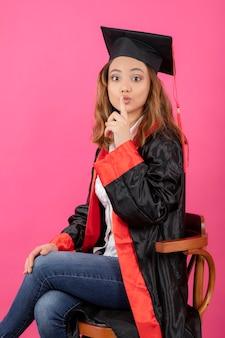 ピンクの壁に静かな卒業式のガウンとジェスチャーを身に着けている女子学生の肖像画。