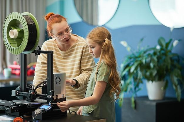 Портрет учителя, помогающего милой девушке с помощью 3d-принтера во время урока инженерии и робототехники в современной школе, копирование пространства