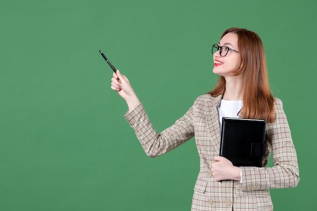 緑にメモ帳を保持している女性教師の肖像画